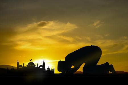 orando: Silueta de las personas musulmanas rezando en la puesta del sol. Foto de archivo
