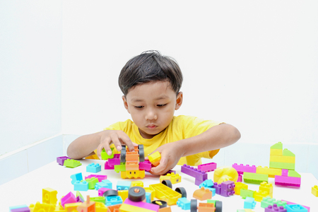 assiduous: boy play with construction set in the room background.