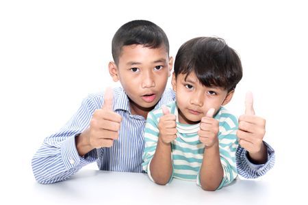 very good: Two brother  boy showing thumbs up gesture  mean very good.