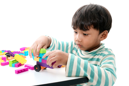 assiduous: Asian boy play with construction set in white background,