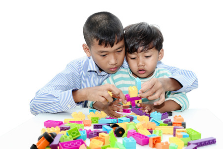 assiduous: Two brother asian boy play with construction set in the room background.