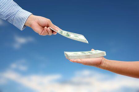 corporate greed: woman hand sent dollar money to men hand.