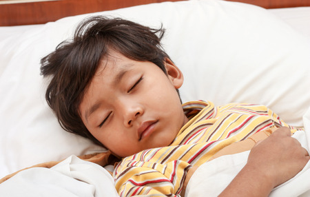 home health care: Little boy sleeping on bed Stock Photo
