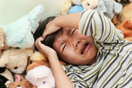 Little  boy crying on woll dolly background Stock Photo