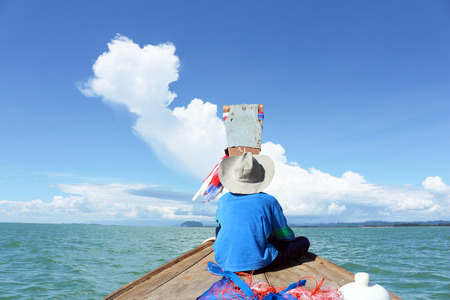 sea fishing: A boy in fishing boat go to the sea at blue sky of the day.