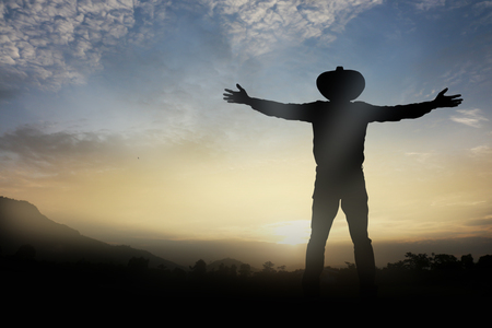 outstretched arms: Man wore hat outstretched arms at   beautiful sunrise. Stock Photo
