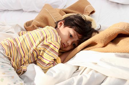 personne malade: Petit garçon endormi sur le lit dans le soleil du matin brille.