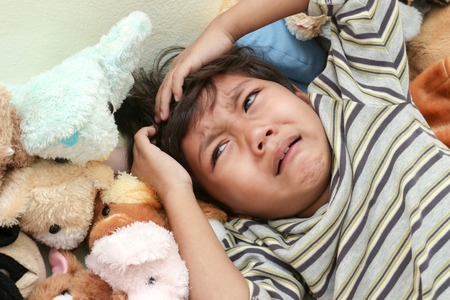 woll: Little  boy crying on woll dolly background Stock Photo