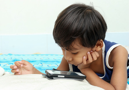 smart boy: Little boy play a smart phone on the bed Stock Photo