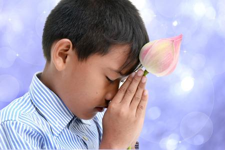 thai buddha: Little buddhist boy praying to buddha with lotus on bokeh background.