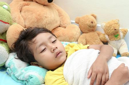 ベッドで寝ている少年 写真素材