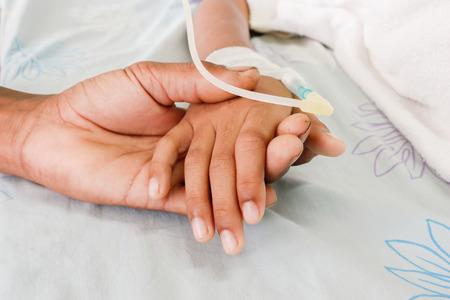 hombre pobre: pobre hombre mano que sostiene la mano del ni�o, que los pacientes con fiebre tienen tubo IV. Foto de archivo