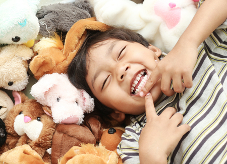 dolly: Happy big laughing asian boy on Dolly wool background. Stock Photo