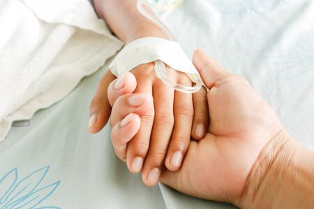 child's: mother holding childs hand who fever patients have IV tube.