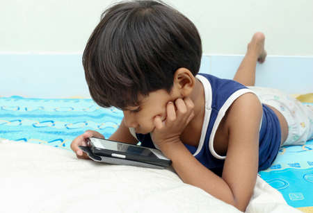 little boy: Little boy play a smart phone on the bed Stock Photo