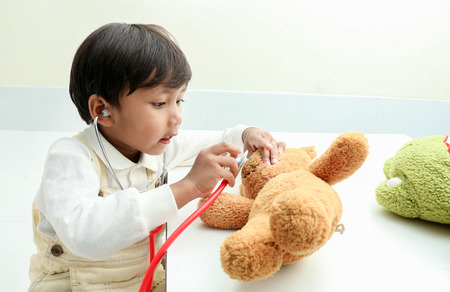 adorable child: Asian boy play with bear  in the room.