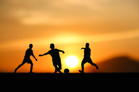 Silhouette of the children play football at sunset. Imagens