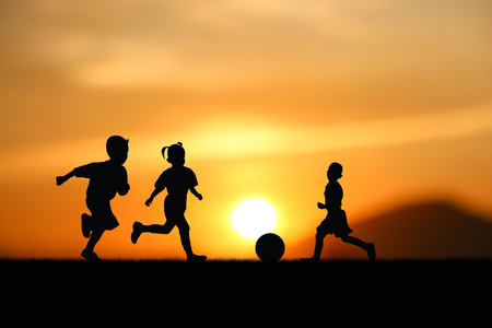 ni�os jugando: Silhouette of the children play football at sunset. Foto de archivo