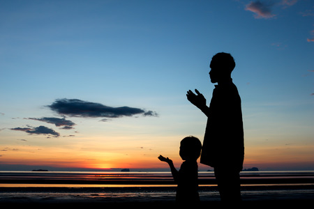 Father and son praying under sunset sky.