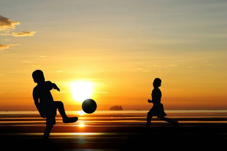 hermanos jugando: Silhouette of  brothers playing together on the beach at sunset.