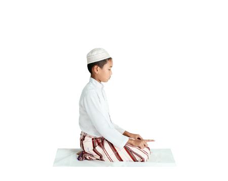 afro arab: Muslim boy praying on the white carpet.
