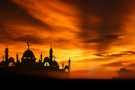 A silhouette of a mosque at sunset.