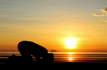 A silhouette of islamic prayjng at sunset. Stock Photo