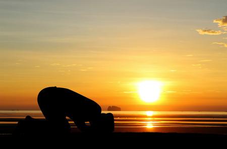 Een silhouet van islamitische prayjng bij zonsondergang. Stockfoto