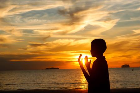 jongen bidden bij zonsondergang op het strand. Stockfoto