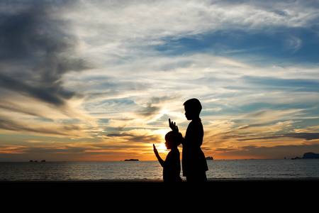 Two brother praying at sunset on the beach. Stock Photo