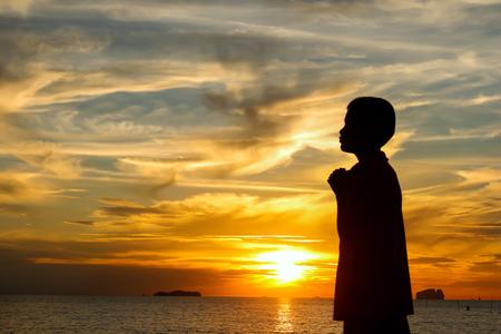 宗教、信仰、祈りと賛美の日没の概念でビーチで挙手の少年のシルエット。
