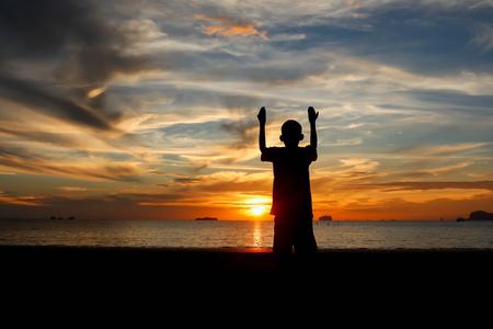 familia cristiana: Dos niño rezando en la puesta del sol en la playa.