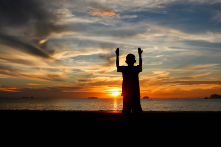 Two boy praying at sunset on the beach.