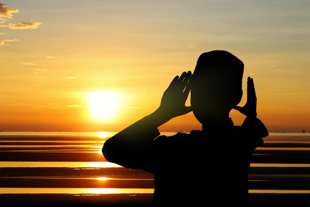 family church: The boy praying at sunset on the beach. Stock Photo