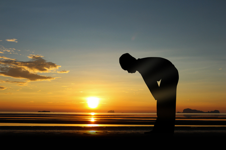The muslim boy praying at sunset on the beach.