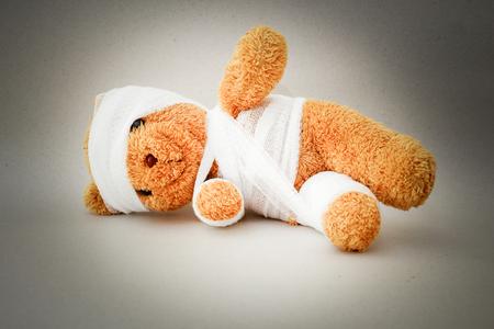 Teddybeer met pleister op een grijze achtergrond.