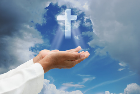Human hands praying over the cross and amazing light. Stock Photo