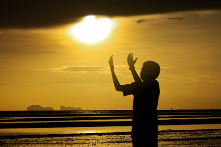 devout: A silhouette of  boy prayjng at sunset. Stock Photo
