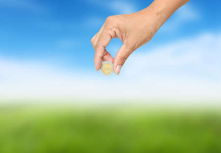 corporate greed: Women hand sent some money  on nature background. Stock Photo