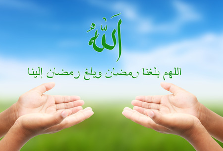 reached: Hand of child pray to God and Arabic Inspirational quote is pray to allah before ramadan comes ,means Oh allah we reached ramadan and ramadan reached us Stock Photo