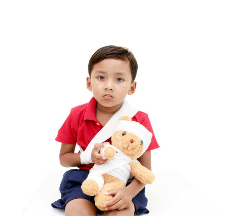 grimace: Children injured has a grimace and showing his broken arm and bandaged at head.with clipping path.