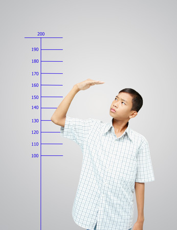 Young boy measuring his growth and worry about his height.