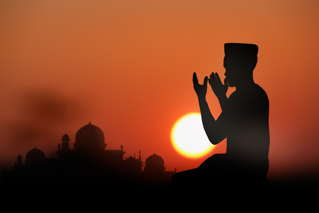 trust god: A silhouette of islamic prayjng at sunset. Stock Photo