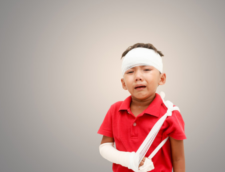 ni�os actuando: Children injured has crying and showing his broken arm and bandaged at head,a boy is acting for patient.