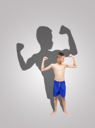 slim boy with bodybuilders silhouette behind him Stock Photo