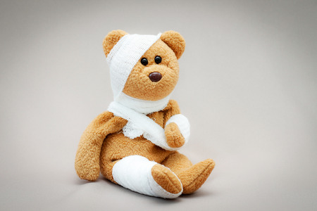Teddy bear with bandage on gray background.