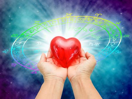 Mano holnding corazón rojo sobre fondo azul del concepto del horóscopo y el amor.