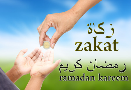 women hand give some money for child .Arabic text is spell zakat and ramadan kareem ,This means the donation is important in Ramadan. Stock Photo