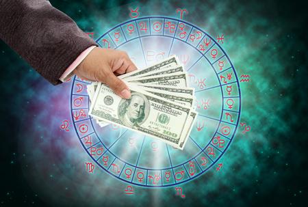mano que sostiene el dinero en el concepto horóscopo. Foto de archivo