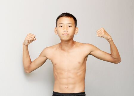 bodybuilding boy: Asian teenage boy who is bodybuilding his smile and happiness in gray background .